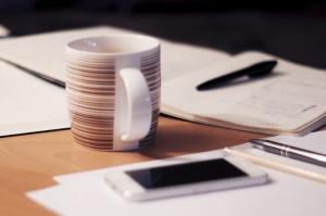 Schreibtisch mit Handy und Arbeitsmaterial