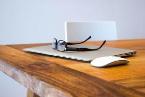Geschlossener Apple Macbook mit Mouse und Brille